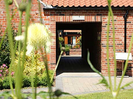 A view through the entrance to our self catering cottages and the courtyard garden.